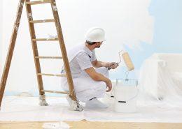 maalari levittämässä seinämaalit seinään telalla