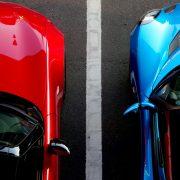 auton kestopinnoita suojaamassa sinistä ja punaista autoa